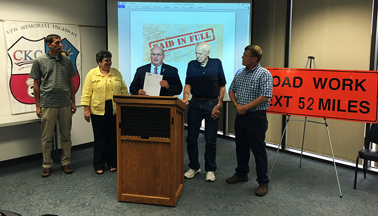 Larry Craig presents MoDOT the paperwork to confirm its final payment. Pictured are: (l - r) Kevin James, MoDOT Northeast District Engineer; Roberta Broeker, MoDOT Chief Financial Officer; Craig; Tom Boland, and Lyndon Bode, who served as secretary for the U.S. 36 TDD Board of Directors.