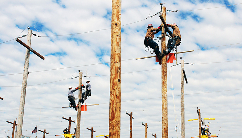 Electric Linemen on Utility Poles
