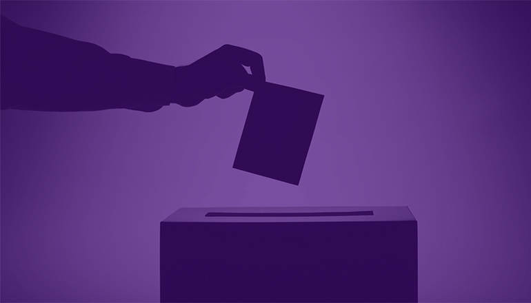 Hand dropping ballot in voting box