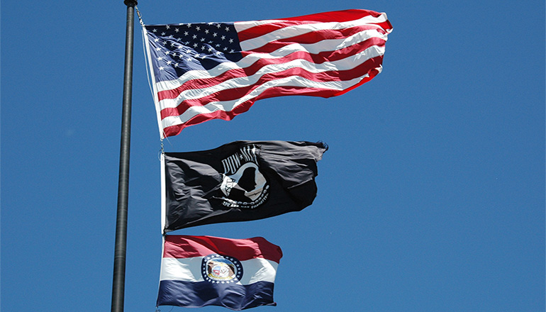 The American flag, the P.O.W. flag, and the Missouri State flag (Photo by Senior Master Sgt. Mary-Dale Amison)