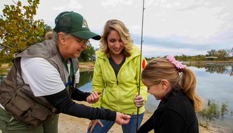 Little girl with mother and MDC agent getting ready to fish
