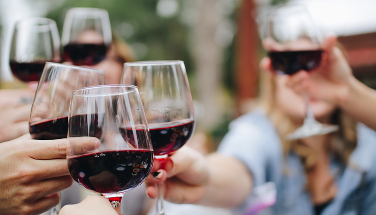 People holding glasses of wine (Photo by Kelsey Knight on Unsplash)
