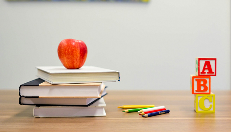 School or education or apple on books with colored pencl and childrens blocks