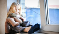Child sitting on window sill (Children)