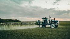 Farmer spraying with a tractor in a field