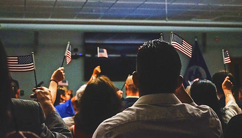 Immigrants waving US Flags