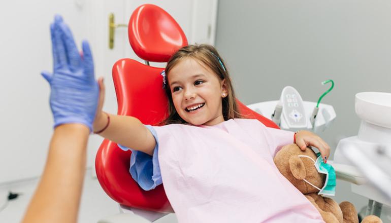 Little girl (child) sitting on dental chair and having dental treatment