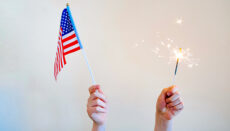 Hands holding U.S. Flag and sparkler