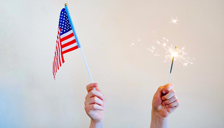 Hands holding U.S. Flag and sparkler