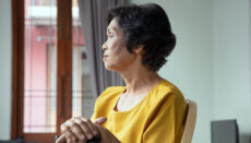 Sad and lonely old senior woman sitting alone in living room, concept of lonely retirement or retirement home