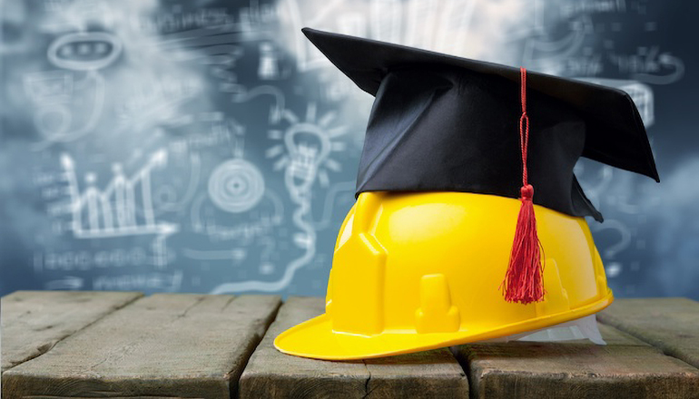 Graduation cap on hardhat (apprentice or education or school or jobs)