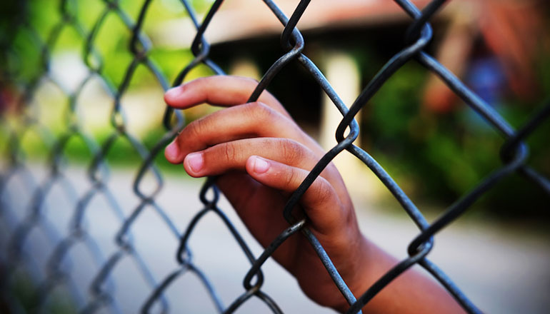 Hand in fence (Juvenile or law enforcement or jail or prison)