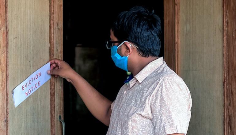 Man finding eviction notice on door (Photo courtesy Missouri News Service)
