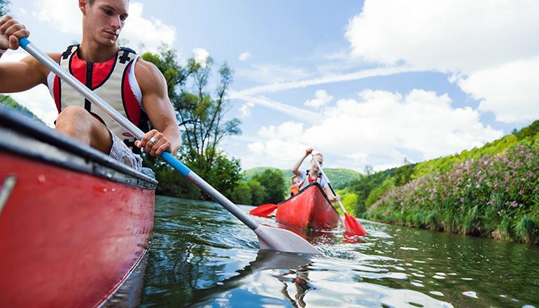People kayaking on waterway