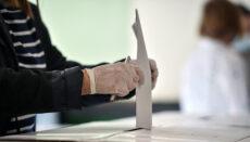 Person casting a vote into the ballot box during corona virus pa