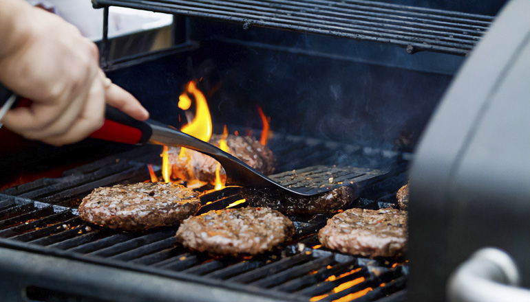Photo of person cooking on outdoor grill (Courtesy of Unsplash)