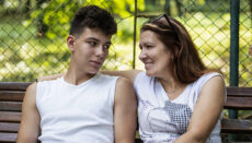 A middle-aged woman is good spending time with her son in a park