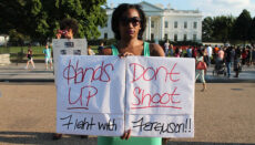 Black woman holding hands up don't shoot sign