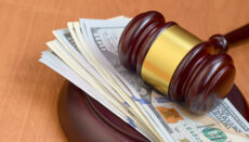 Judge gavel and money on brown wooden table. Many hundred dollar bills under judge malice on court desk. Judgement and bribe