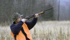 Woman shooting shotgun in field