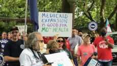 Demonstrators stand outside of the Governor's Mansion in Jefferson City on July 1, 2021 and hold signs urging Gov. Mike Parson to fund voter-approved Medicaid expansion